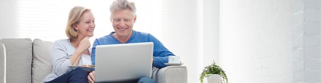 cheerful mature couple using laptop
